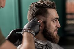Brutal handsome man with beard sits at a barber shop. Barber shaves hairs at the side. stock photo