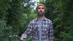 Brutal hipster guy in park carrying fixie bicycle. Hipster guy in town carrying fixie bicycle stock video