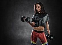 Brutal idrotts- kvinna som upp pumpar muscules med hantlar Royaltyfri Foto