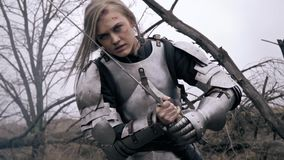 Brutal Jeanne Dark in armor becomes in combat posture with a sword. Effective blonde in medieval armor prepares to fight stock video footage