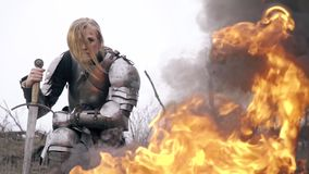 Brutal knight woman on the background of a fire, slow motion