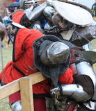 Brutal Knights battle in iron armor with bladed weapons Stock Images