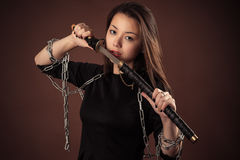 Brutal korean girl with sword. On brown background Stock Photo