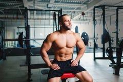 Brutal kroppsbyggare bredvid skivstånger Ung sportman med sex packeabs på en idrottshallbakgrund Aktivt livsstilbegrepp Arkivfoton