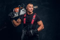 Brutal logger posing with a chainsaw on his shoulder and looks sideways. Young brutal logger posing with a chainsaw on his shoulder and looks sideways royalty free stock image