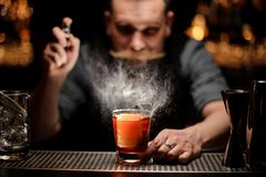 Brutal bartender pours an alcohol cocktail using sprayer stock image
