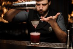 Bartender makes an alcohol drink with shaker and sieve. Brutal male bartender with beard makes a red alcohol drink with steel shaker and sieve at bar counter stock images