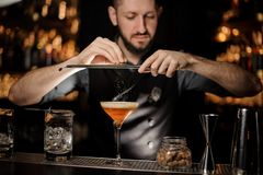 Bartender with beard pouring alcohol cocktail using grater royalty free stock image