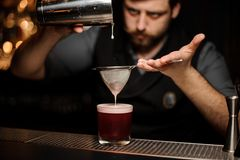 Bartender preparing alcohol drink with shaker and sieve. Brutal male bartender with beard preparing red alcohol drink with steel shaker and sieve at bar counter stock photography