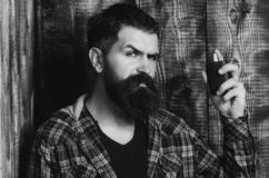 Brutal man applying perfume or cologne from black bottle. Perfume. Brutal man or bearded caucasian hipster with grey hair, long beard and moustache applying stock photo