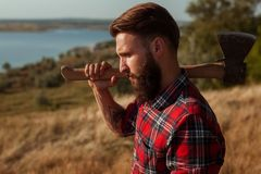 Brutal man with axe on nature Stock Photos