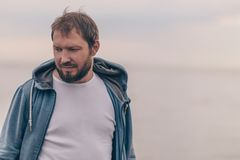 Brutal man with a beard against the background of an empty sky and sea royalty free stock image