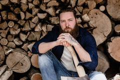 Brutal man with a beard dressed in casual clothes with tattoos on his hands holds the ax sitting near the stacked wood royalty free stock photos