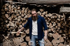 Brutal man with a beard dressed in casual clothes with tattoos on his hands holds the ax sitting near the stacked wood royalty free stock photo