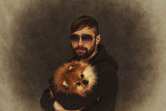 Brutal man with a beard and fashionable hairstyle with a dog in her arms Royalty Free Stock Photos
