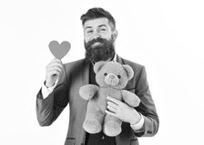 Brutal man with beard and happy face. Declaration of love. Style, fashion concept. Happy bearded holds red heart and teddy bear. Miss you, Valentines day Stock Photo
