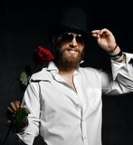 Brutal man with beard and hat holding red rose for date stock image