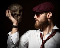 Brutal man with beard and mustache in hat cap and white shirt with tie on dark hold skull. Brutal man with beard and mustache in hat cap and white shirt with tie royalty free stock image