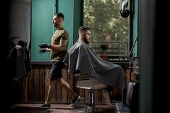 Brutal man with beard sits in a chire at a barber shop. Handsome barber passes next to him royalty free stock photos
