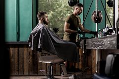 Brutal man with beard sits in a chire at a barber shop. Handsome barber takes the hairclipper royalty free stock photo