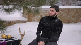 A man in a black suit under heavy snow. Gothic. A brutal man with a beard sitting at a table outdoors in heavy snow, the table is decorated with black cloth stock video footage