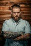 Brutal man with beard and tatoos. Brutal man with beard and tatoos possing over wooden wall Royalty Free Stock Image