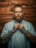 Brutal man with beard and tatoos. Brutal man with beard and tatoos possing over wooden wall Royalty Free Stock Photo
