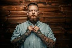 Brutal man with beard and tatoos. Brutal man with beard and tatoos possing over wooden wall Stock Photos