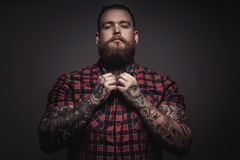 Brutal man with beard and tattoes. On his arms. Isolated on grey background Stock Images