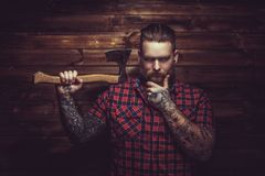Brutal man with beard and tattooe. Brutal man with beard and tattooe holding axe over wooden wall stock photography