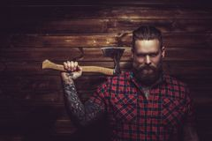 Brutal man with beard and tattooe. Brutal man with beard and tattooe holding axe over wooden wall royalty free stock photo