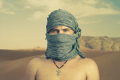 Brutal man in desert. Photo of brutal man in Bedouin scarf in desert Stock Images