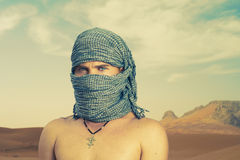 Brutal man in desert. Photo of brutal man in Bedouin scarf in desert Royalty Free Stock Photos