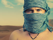 Brutal man in desert. Photo of brutal man in Bedouin scarf in desert Royalty Free Stock Photo