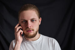 A brutal man in full face with a mustache and beard. With slicked hair with natural light on a black background puzzled talking on mobile phone stock photos