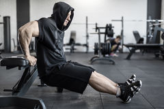 Brutal man in gym. Active man with heavy muscles does lifting on the bench in the gym. He wears black hooded sleeveless, black shorts and dark sneakers. Shoot Royalty Free Stock Photo