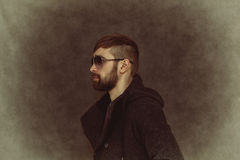 Brutal man-hipster with fashionable hairstyle and beard Stock Photos