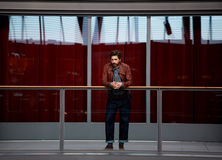 Brutal man in a leather jacket burgundy leaned on the railing. Full length portrait of stylish mature man leaning on the glass fence while standing in interior royalty free stock photography