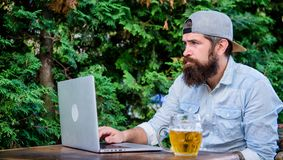 Brutal man leisure with beer and laptop. Finally friday. Hipster relax sit terrace with beer. Bearded hipster freelancer. Enjoy end of working day with beer mug stock photography
