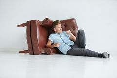 Brutal man lying next to a brown leather armchair Stock Photo