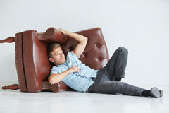 Brutal man lying next to a brown leather armchair Stock Photography