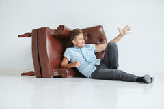 Brutal man lying next to a brown leather armchair Stock Images