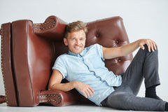 Brutal man lying next to a brown leather armchair Royalty Free Stock Image