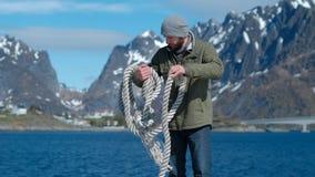 Brutal man med ett rep p? hans skuldra mot bakgrunden av bergen och den bl?a himlen arkivfilmer