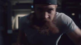 Brutal man med ett skägg som flyttar intensivt hans händer på ellipsoiden arkivfilmer
