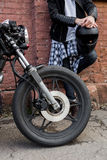 Brutal man near his cafe racer custom motorbike. Stock Images