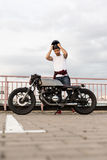 Brutal man near his cafe racer custom motorbike. Handsome happy rider man with beard and mustache put on black moto helmet and sit on his classic style biker royalty free stock photography
