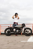 Brutal man near his cafe racer custom motorbike. Handsome happy rider guy with beard and mustache put on black moto helmet and sit on his classic style biker stock photography