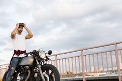 Brutal man near his cafe racer custom motorbike. Stock Photo