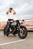 Brutal man near his cafe racer custom motorbike. Handsome rider man with beard and mustache posing while take off black moto glasses near classic style biker stock photos